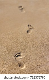 Footprints in the sand, three steps with a low depth of field