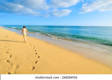 Footprints in sand with young woman tourist walking on beach in Morro Jable, Fuerteventura island, Spain