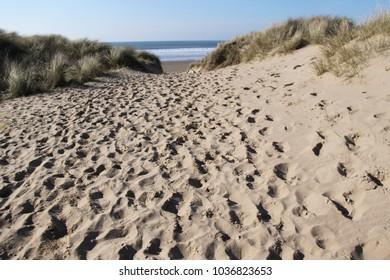 footprints in sandy walk to beach