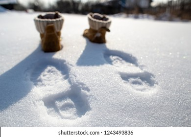 Footprints and shoes on pure white snow on a cold sunny day, in the blurry background.