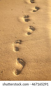 Footprints at sunset with golden sand. beach, wave and footsteps at sunset time