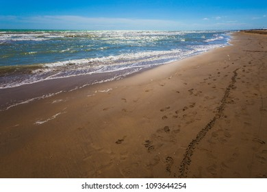 Footprints and traces on sandy beach beaten by waves, Bibione, Veneto, Italy