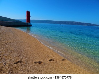 Footprints walking to the Adriatic sea at a scenic beach on the Croatian Cres island, with crystal clear water, blue sky and a red lighthouse in the background in summer