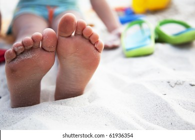 foots of little girl at the beach and slates nearby
