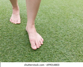 Foots steping forward on grass field close up.