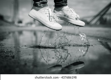 Foots of a woman in a sport shoes flying over a puddle during jumping. Close up shot of foots over the water