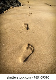 Footstep Path on the sandy beach. The shadowing in these foot prints gives the effect of making the footprints look inverted in one moment then an outward 3d illusion in another moment.