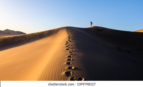 Footsteps along the top of the sand dunes in Death Valley National Park in California, with a hiker photographing the sunset in the background.
