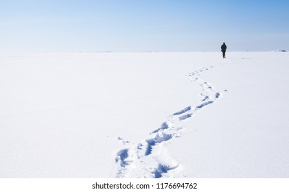 Footsteps of lonely person walking on frozen sea covered with snow. Russian winter