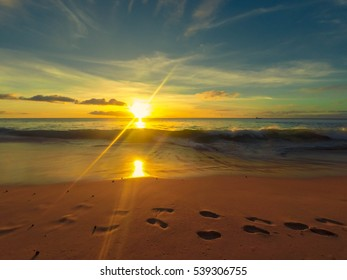 Footsteps on the beach with a warm sunset