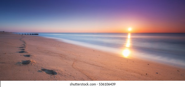 Footsteps in the sand during a sunrise panorama