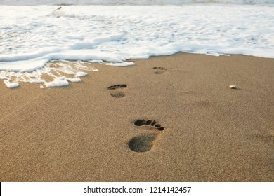 Footsteps in the sand to the foamy wave