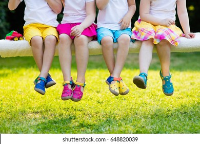 Footwear for children. Group of preschool kids wearing colorful leather shoes. Sandal summer shoe for young child and baby. Preschooler playing outdoor. Child clothing, foot wear and fashion.