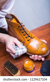 Footwear Cleaning Ideas. Professional Male Shoe Cleaner Using Cloth and Brush For Tan Derby Boots. Working in Workshop. Vertical Image Orientation
