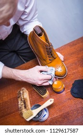 Footwear Cleaning Ideas. Professional Male Shoe Cleaner Using Cloth and Brush For Tan Derby Boots. Working in Workshop. Vertical Image