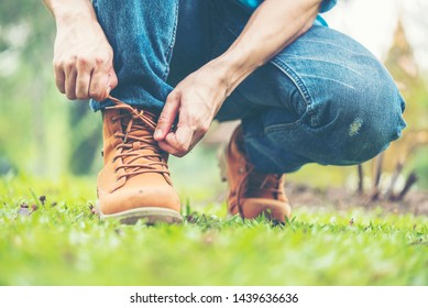 Footwear concept.Handsome man wear jeans knelt down to do up his shoelaces. Preparing before go to party. Brown boots on green grass. close up man hands tie up shoes.