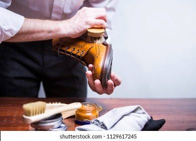 Footwear Concepts. Closeup of Male Hands with Polishing Brush for Tan Brogue Derby Boots. Bunch of Accessories for Cleaning In Front. Horizontal Image Orientation
