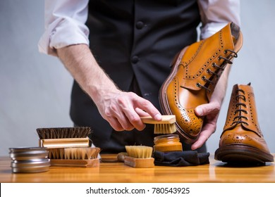 Footwear Concepts. Closeup of Mans Hands Cleaning Luxury Calf Leather Brogues with Special Accessories And Tools. Horizontal Image Composition