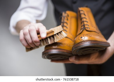 Footwear Concepts and Ideas. Closeup of Hands of Man Cleaning Premium Derby Boots With Variety of Brush.Horizontal Image