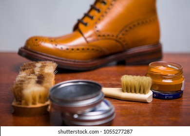 Footwear Concepts and Ideas. Closeup of Premium Male Brogue Tanned Boots with Lots of Cleaning Accessories on Foreground.Horizontal Image Orientation