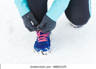 Footwear during winter time and workout outside. Shot of tying sholaces. Sporty trainers for wintry weather and doing exercises.