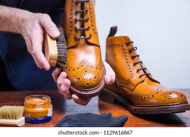 Footwear Ideas. Hands of Professional male Shoes Cleaner with Cleaning Brush For Tan Derby Boots. Working in Blue Apron in Workshop. Horizontal Image Orientation