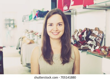 Footwear shop smiling girl posing with different shoes