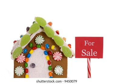 A 'For Sale' sign next to a gingerbread house.