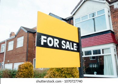 'For Sale' sign outside of a terraced house in the UK.