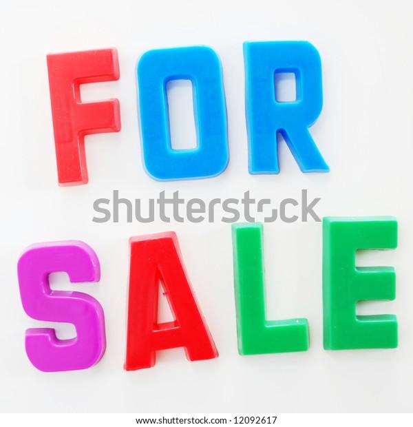 'For Sale' written on fridge door with fridge magnet alphabet letters.