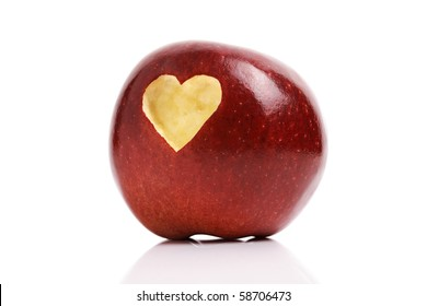 Forbidden fruit red delicious apple with a love heart shape bitten into the flesh