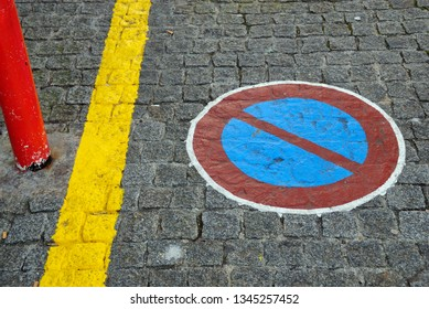 Forbidden parking sign painted on paving stones, close to yellow line and red pylon.