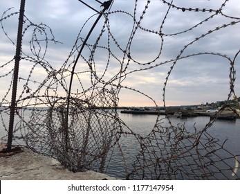 the forbidden sea. a fence enclosing a picturesque sea sunset