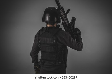forces, airsoft player with gun, helmet and bulletproof vest on gray background