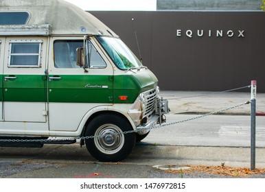 Ford Econoline van occupied by homeless dweller parked on public street near Equinox luxury fitness gym - Palo Alto, California, USA - Circa 2019