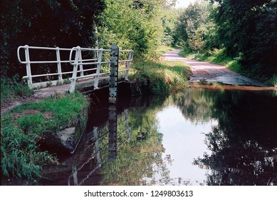 A ford and pedestrian bridge on a country lane in Norfolk, England (analog film photo).