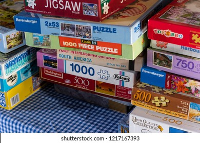 Fordingbridge, England - October 22, 2018: Different Jig Saw Puzzle boxes on a table with a blue and white cloth.