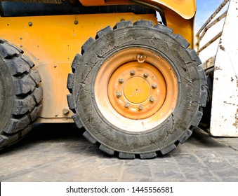 A fore wheel and a heavy duty tyre, construction site machinery.