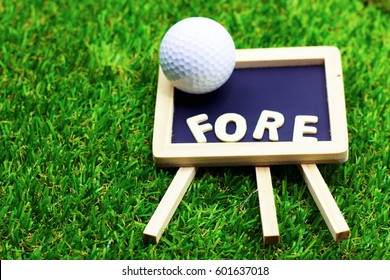 """Fore wording with golf ball are on green grass. """"Fore!"""", originally an Australian interjection, is used to warn anyone standing or moving in the flight of a golf ball."""