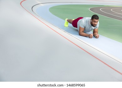Forearm plank exercise. Dark-haired young sportsman doing a forearm plank exercise at the stadium before running