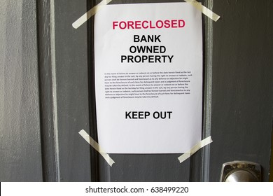 Foreclosed property notice taped on  a house door property.