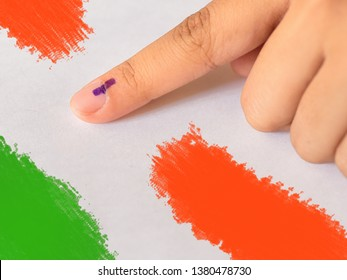 Forefinger marked with electoral ink against white background with Indian flag colors. Parliamentary (Lok Sabha) Elections 2019, India.