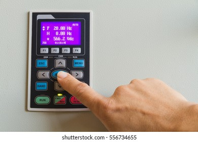 Forefinger touch on enter switch on control panel for machine controller.
