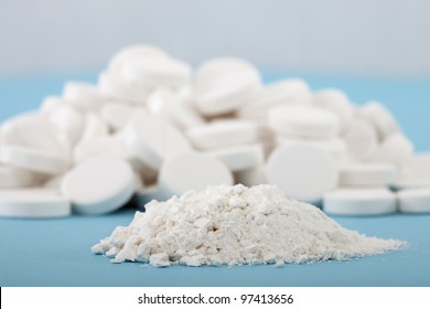 forefront of crushed pills on a blurred background of whole tablets
