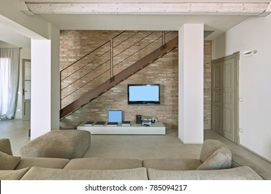foregound  the fabric sofa in the contemporary living room, on the background the brick wall and the iron staircase that leads to second floor