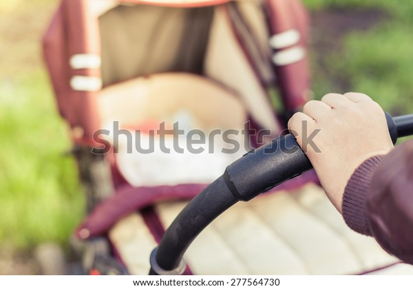 foreground of baby carriage and mothers hand at outdoor, spring or summer season with fresh green background