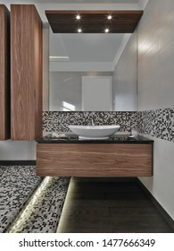 in the foreground the cabinets sink  with  conuter top washbasin and wood floor in the modern bathroom