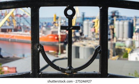 In the foreground can be seen an anchor in an iron fence. Back blurred the background you can see sea trade port and the orange ship.