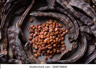 In the foreground, carob pods and in the center carob seeds to obtain locust bean gum, a thickener used above all to prevent the crystallization of ice cream and thicken other products