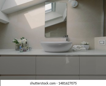 in the foreground the counter top washbasin in the modern bathroom in the attic room